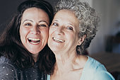 Senior lady and her daughter laughing and posing at camera