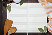 open notebook for writing recipes and kitchen spoons, background concept, top view