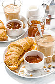 croissants with jam and coffee with milk for breakfast, vertical
