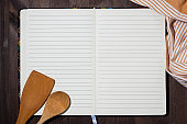 open notebook for writing recipes and kitchen spoons on a wooden background, closeup