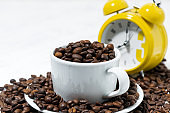 cup with coffee beans and an alarm clock, conceptual photography