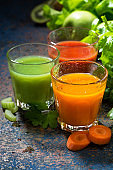 glasses of fresh vegetable juice from carrots, tomatoes and herbs, vertical, closeup
