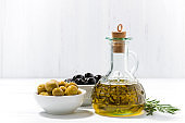 bottle with olive oil and bowls with olives on white table