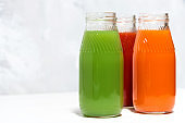 colorful vegetable juices in bottles on white background, closeup