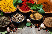 assortment of various spices and herbs on a wooden background, closeup