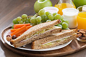 lunch with sandwiches, drinks and fresh fruit on wooden table