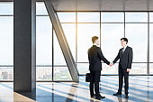 Businessmen shaking hands in meeting room