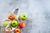 fresh organic apple in reusable shopping bag.
