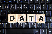 Text of the word DATA on wooden cubes on a black keyboard