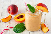 Healthy peach smoothie in a mason jar glass, close up against a white wood background