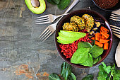 Healthy vegan buddha bowl with falafels, beet quinoa, avocado, and vegetables on dark stone, corner border with copy space.