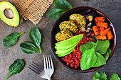 Healthy vegan buddha bowl with falafels, beet quinoa, avocado, and vegetables on dark stone