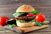 Portobello mushroom vegan burger on a wooden serving board against a dark wood background