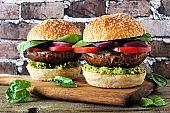 Portobello mushroom vegan burgers on a wood serving board against a dark brick background