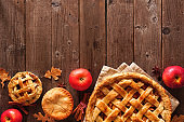 Homemade autumn apple pie, top view bottom border over a rustic wood background