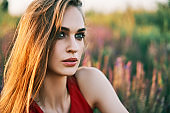 Portrait of beautiful young woman posing in sage field in summer sun