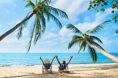 Happy couple with arms up relax on the beach enjoy beautiful sea on the tropical island