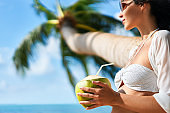 Beautiful young woman enjoy coconut drink and relax on tropical beach with palm tree