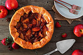 Apple strawberry autumn pie, above view table scene over a rustic wood background