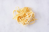 Fresh linguine pasta, top view against white marble