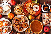 Autumn food table scene with pies, appetizers and desserts. Top view over a rustic wood background.