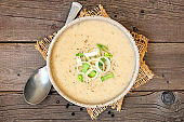 Potato and leek soup, top view table scene on a rustic wood background