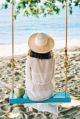 Back view of happy woman relax on swing on beautiful paradises beach