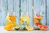 Variety of citrus infused detox water drinks in mason jars against blue wood