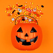 Halloween Jack o Lantern bucket with spilling candy, top view on an orange background
