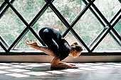 Young beautiful woman doing yoga asana baby crow pose on triangular window background