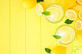Summer lemonade top view corner border on a yellow wood background