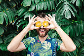 Young bearded man holding slices of orange tangerine in front of his eyes, laughing