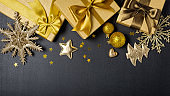Golden gift boxes with shiny brown satin bow and glittering christmas tree toys