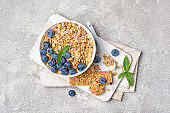 Top view of oatmeal with fresh blueberry in white bowl and granola energy bar