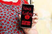 woman hand holding  Black Friday marketing label in the screen, Black Friday advertisement banner in a mobile phone screen, shop now