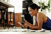 Smiling athletic woman drinking detox smoothie and while text messaging on cell phone.
