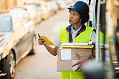 Black female delivery person working in the city.