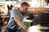 Pensive manual worker working with CNC machine in a factory.