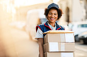 Portrait of happy African American deliverer with packages.