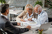 Mature couple examining blueprints while having a meeting with real estate agent.