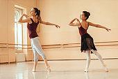 Ballet teacher and ballerina practicing together at dance studio.