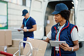 African American delivery woman using touchpad while checking packages.