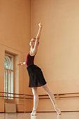 Ballerina rehearsing ballet pose at dance school.