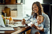 Happy mother with baby son calculating bills at home.