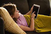 Little girl playing games on touchpad while relaxing on the sofa.
