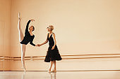 Dedicated ballerina rehearsing with her female instructor at ballet studio.