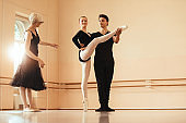 Ballet couple rehearsing choreography with help of their instructor at ballet studio.