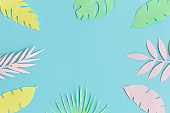 Flat lay of colorful tropical leaves made of paper against blue background minimal creative summer concept.
