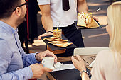 Unrecognizable waiter serving a meal to guests in a restaurant.