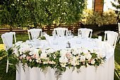 White wedding table setting at outdoor reception.